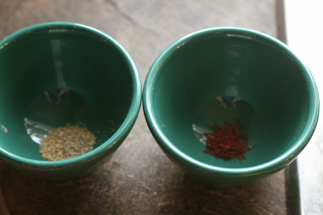 two small bowls, one containing ground cardamom, the other containing saffron threads