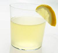 Kenarına yarım bir limon dilimi geçirilmiş bir bardak limonata