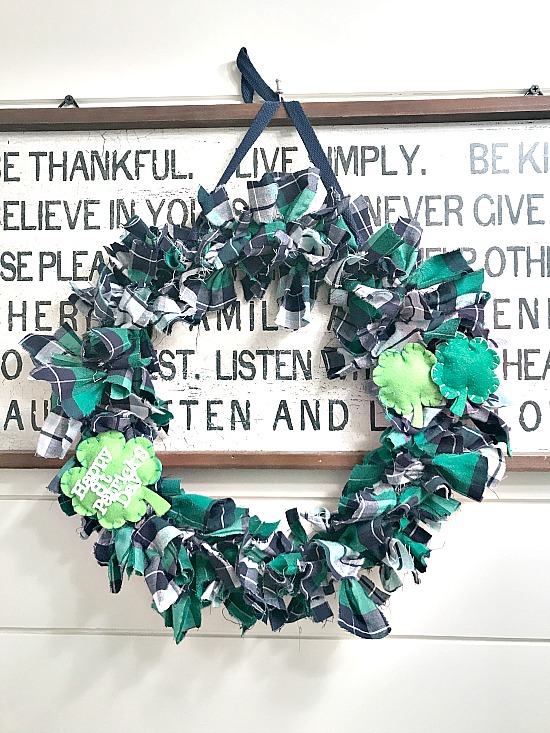 DIY St. Patrick's Day Plaid Rag Wreath hanging on a lettered sign