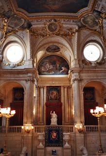 Interior del Palacio Real, con elementos decorativos como estatuas, columnas, lienzos, frescos enmarcados por relieves dorados.