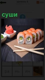 На столе на разделочной доске лежат приготовленные суши, разрезанные на кусочки