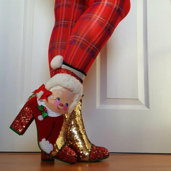 tilted foot wearing Christmas Mrs Claus themed ankle boots and festive tartan tights
