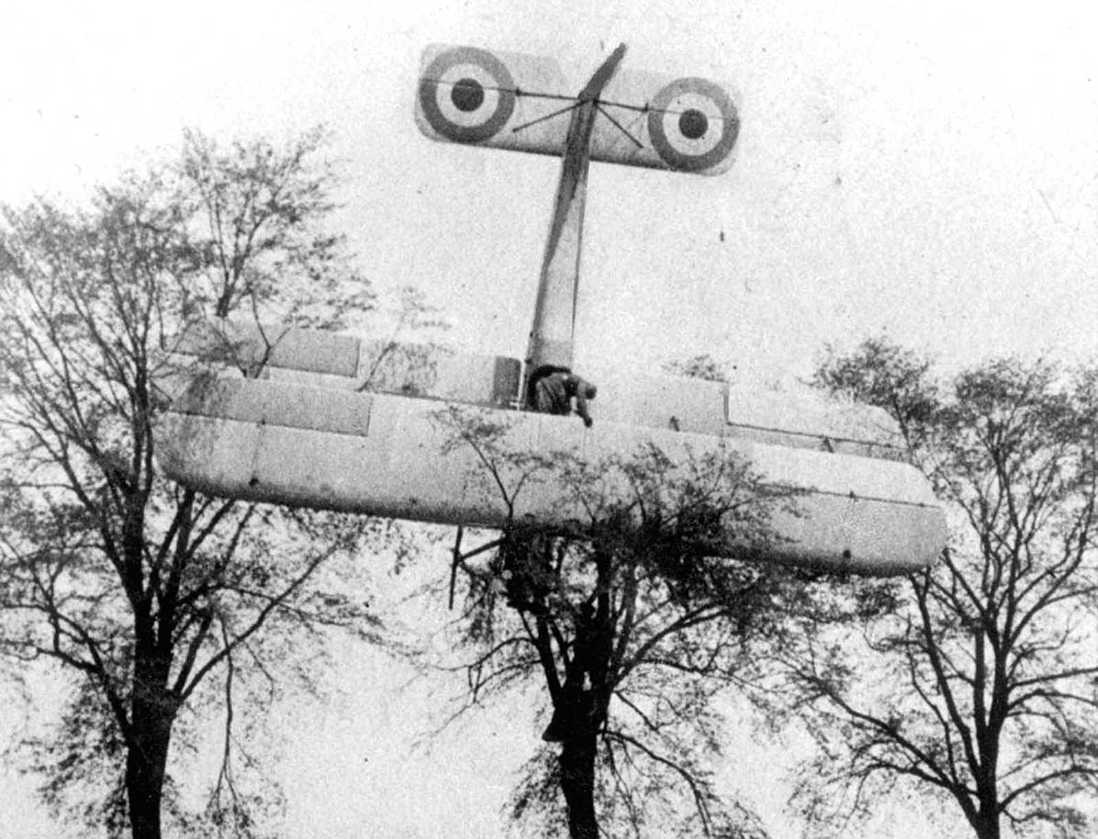 A French pilot made an emergency landing in friendly territory after a failed attempt to attack a German Zeppelin hangar near Brussels, Belgium, in 1915. Soldiers are climbing up the tree where the biplane has landed.