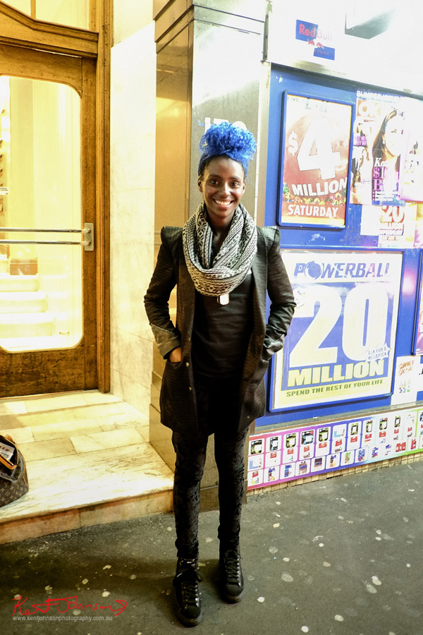 Blue hair, structured jacket, patterned scarf, with black tee and textured black leggings and boots. Photo by Kent Johnson.