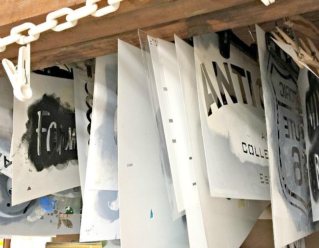 stencil storage in a basement workshop using plastic hangers.
