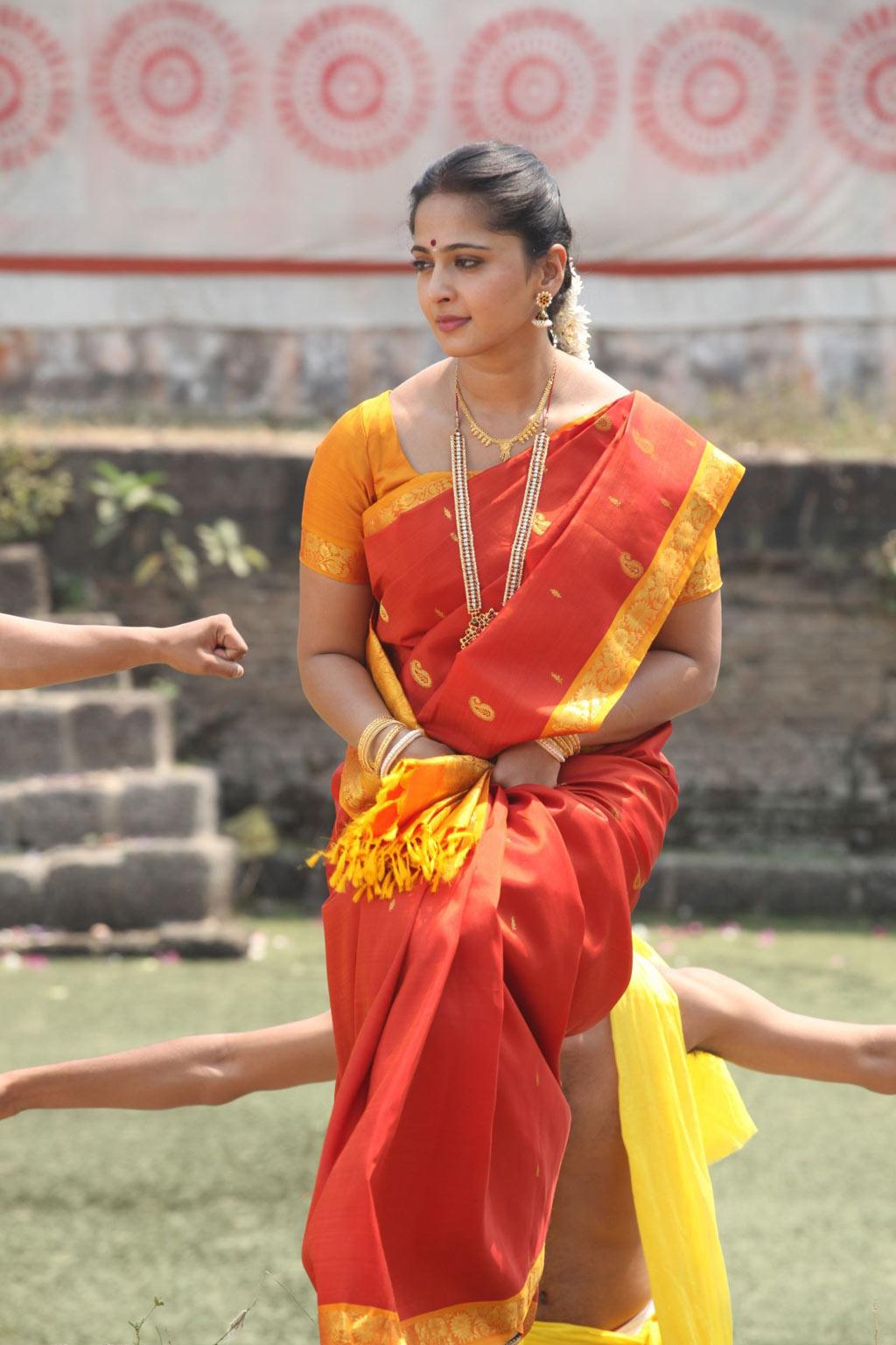 South Indian Girl Anushka Shetty Long Hair Stills In Orange Traditional Saree