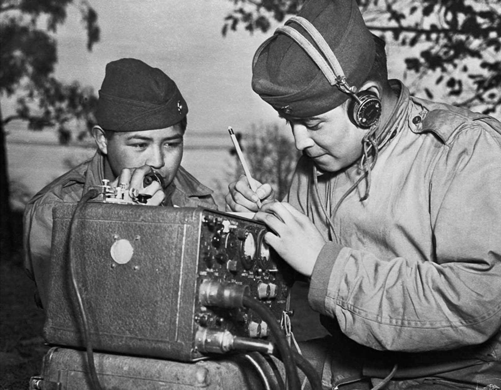 A two-man team of code talkers attached to a Marine regiment relay coded orders over a field radio.