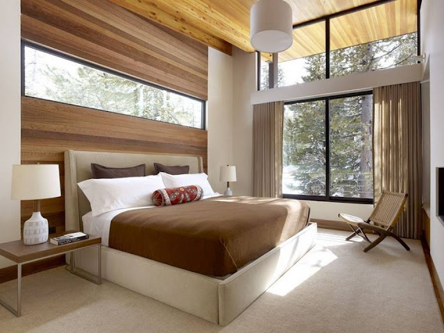 Southwestern Guest Bedroom with flush light, Wall sconce, Concrete floors, Cement fireplace,