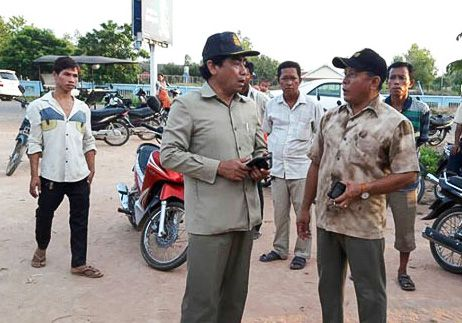 Authorities talk near a canal in Siem Reap's Puok district where three young children drowned on Sunday. National Police