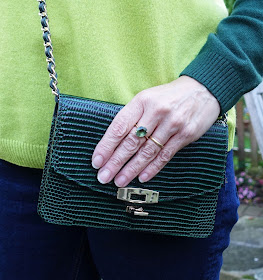 Image showing a compact cross-the-body bag in green leather by Uterque and peridot ring