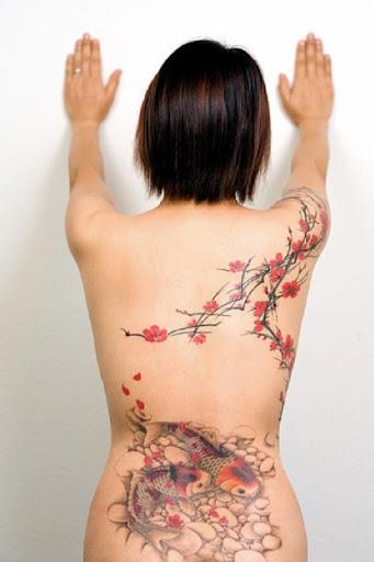 Encantador da flor de cerejeira tatuagem nas costas por Joey Pang. Os finos traços da flor de cerejeira ramos de criar uma perfeita aura para o sereno e tranquilo flores de cerejeira como eles gentilmente olhar sobre um lago com peixes Koi. (Foto: Fontes de imagem)