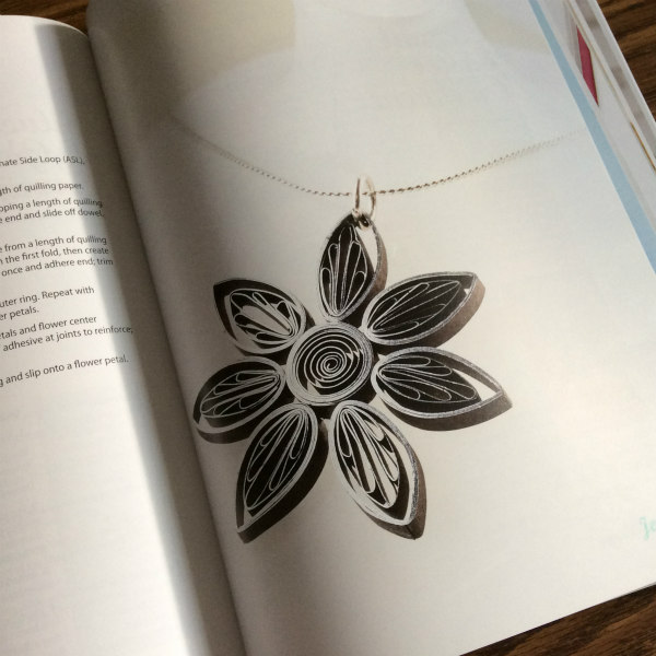 silver and black quilled alternate side loop flower pendant on a fine silver necklace chain