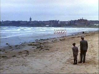 Fotograma de la película Carros de fuego. Muestra un entrenamiento atletas en una playa