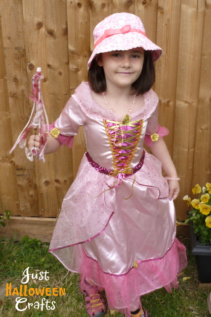 Girl dressed up in a pale pink princess costume with matching hat and wand