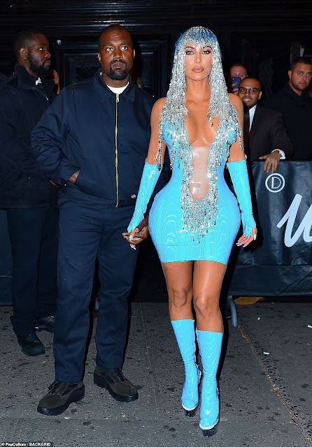 Kim Kardashian looks stunning in a blue plunging latex gown and tinsel wig
