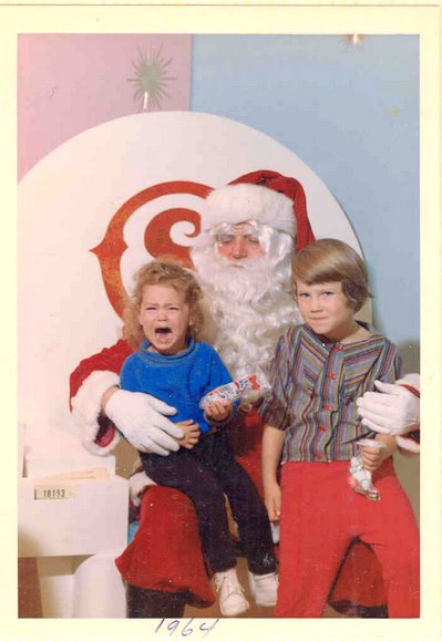 Two girls with Santa, one crying, one bemused