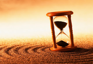 L'immagine rappresenta una clessidra che sovrasta una distesa di sabbia con dei solchi a circolari, nello sfondo è presente un tramonto luminoso
