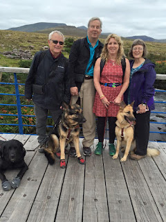 Bob, Mike, Gena and Sue on a bridge with their guide dogs and GPS