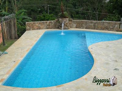 Construção de piscina de alvenaria com o muro de pedra, o piso de pedra com caco São Tomé, a cascata de pedra com a bica d'água e os dormentes de madeira.