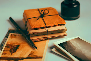 Flash Fiction, Old photographs and pens clutter a white surface