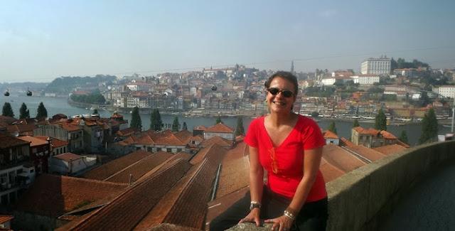 Senhora sentada junto aos telhados das caves de vinho do Porto