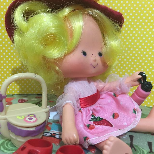 Boneca Maçãzinha pegando uma garrafinha de bebida no seu piquenique