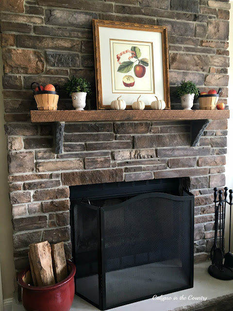 Rustic Stone Fireplace Decorated for Autumn using apples and white pumpkins