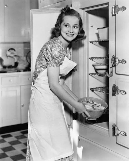 Young Housewife in an apron smiles as she takes a bowl out of the refrigerator c.1930s. Oh Wait and other stories of the Refrigerator. marchmatron.com