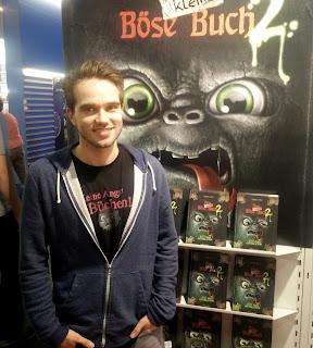 Thomas Hussung vor Regal mit Das kleine Böse Buch 2