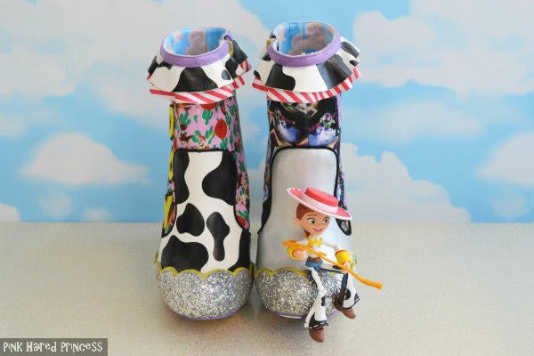 cow print ankle boot sitting aside silver ankle boot both facing forward wit sky wallpaper background and Jessie Toy Story figure sitting across toe