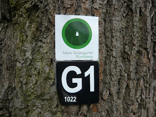 Am Baum hängt ein weißes Schild mit einem grünen Kreis. Darunter ein schwarzes Schild mit dem Buchstaben G und der Zahl 1