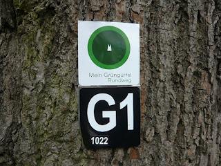 Zwei Blechschilder an einem Baum. Oben ein weißes Quadrat mit einem grünen Kreis, in der Mitte des Kreises symbolisch der Kölner Dom. Darunter ein schwarzes Schild mit der Aufschrift G1