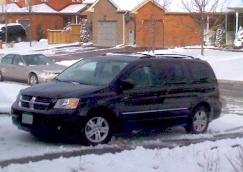 The new van sitting in a snowy driveway.