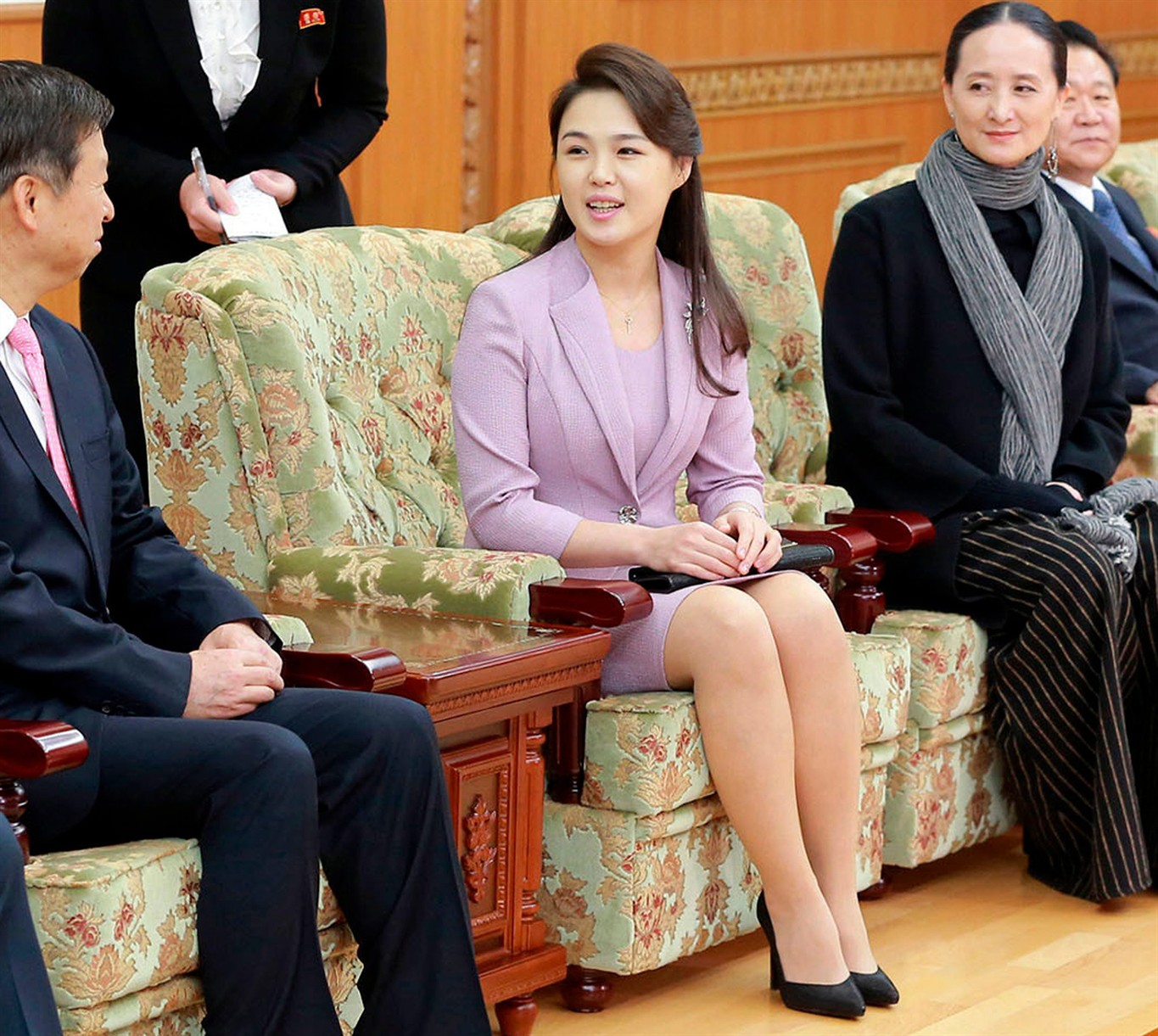 In this April 14, 2018, photo provided by the North Korean government, Ri Sol Ju, center, wife of North Korean leader Kim Jong Un, talks with Song Tao, left, head of the ruling Communist Party's International Department, in Pyongyang, North Korea.