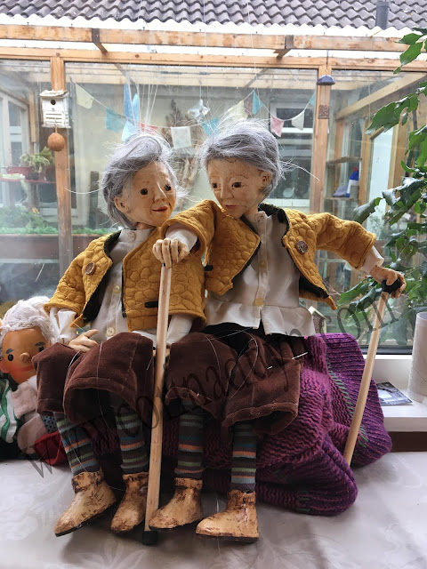 two puppets identically dressed sitting side by side by a window. Reflection puppet project by Corina Duyn