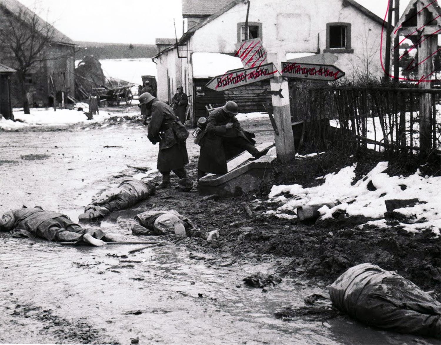 German soldiers strip boots and other equipment from dead American soldiers, 1944