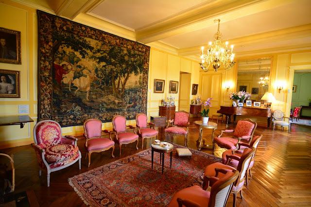 Le salon est organisé autour du piano à queue sur lequel sont posés des portraits de famille ; le décor est du XVIIIème siècle