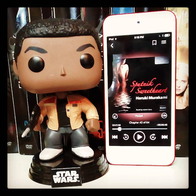 A large-headed Funko Pop bobblehead of Finn from Star Wars stands beside a white iPod with Sputnik Sweetheart's cover on its screen. The cover features a naked Japanese woman submerged to the waist with her back to the viewer. The space around her is pitch black, with the title illuminated in red.