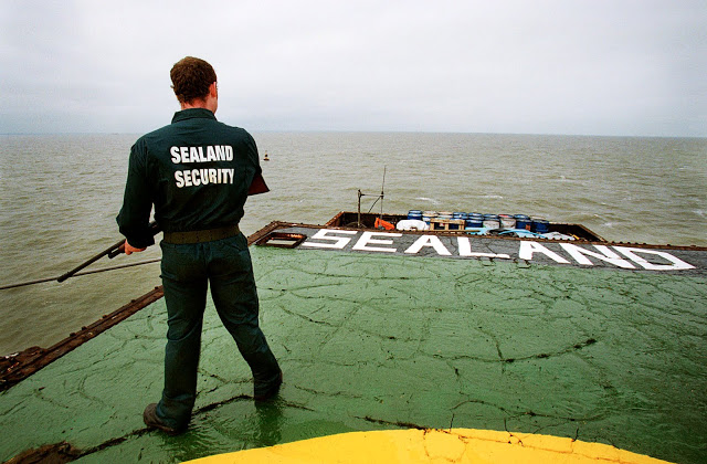 Recent photo of the Principality of Sealand. An armed guard wearing a Sealand Security shirt stands on the platform.  Pirate Radio and Sealand and Other stories of Rock, Radio, and Regulations. Marchmatron.com