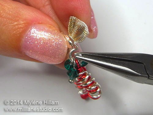 Connecting the candy cane, the emerald crystal components and bow together with a jump ring, using chain nose pliers.
