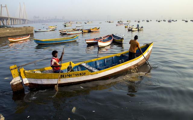 fishermen boat rowing arabian sea worli jetty mumbai koliwada india