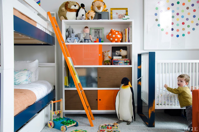 Kid's bedroom with white shelves with orange and brown doors, bunk beds and a crib in matching blue and white frame, orange accents on the ladder and crib and a large framed picture of a circle with colored dots arranged in a circle inside it