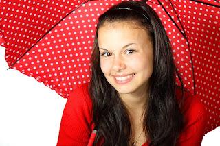 Eine junge Frau, die lächelt und einen geöffnete Regenschirm hält