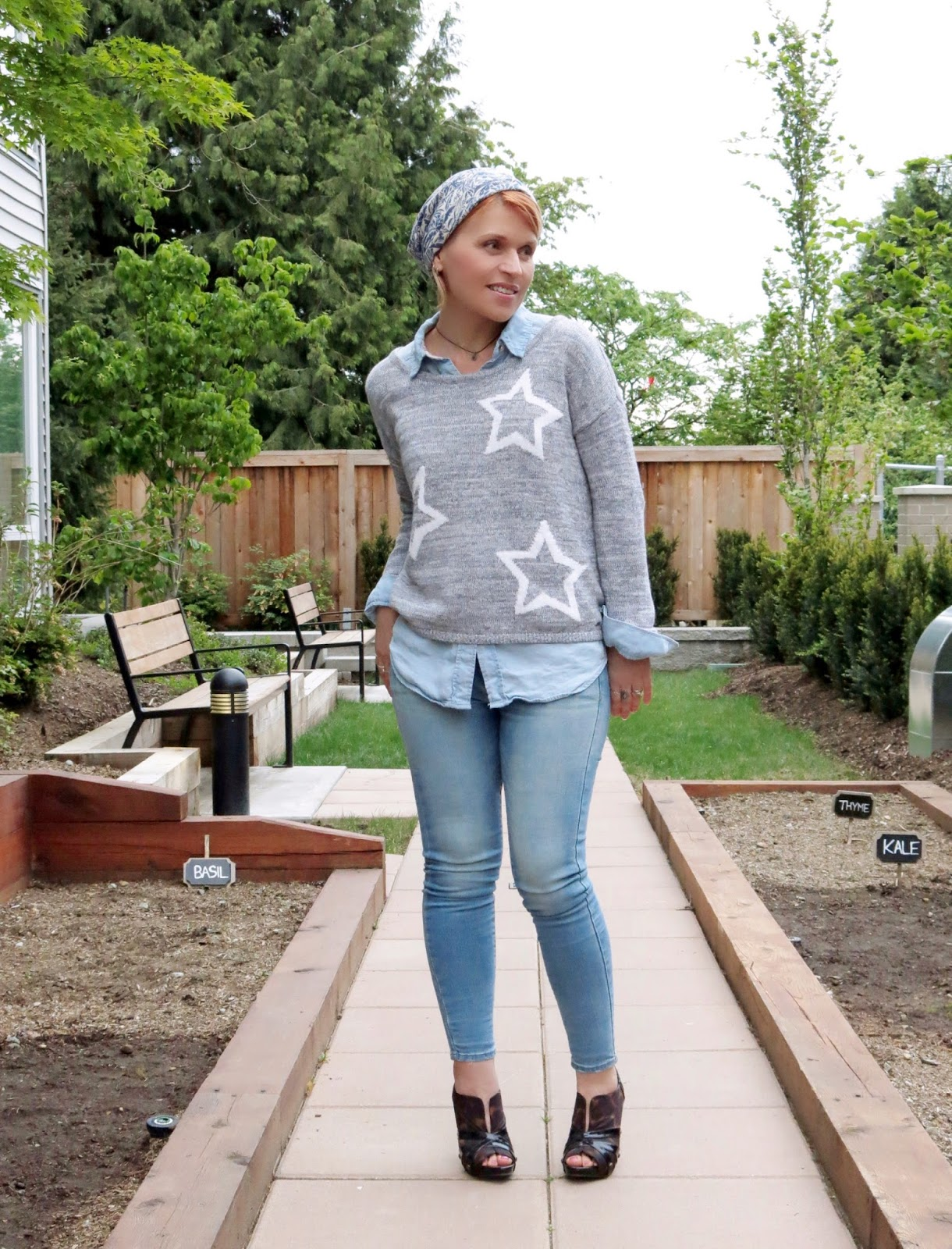 chambray shirt layered under a star-patterned sweater, skinny jeans, floral jersey beanie, and leopard heels