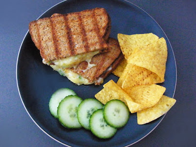 Comfort Cheese Toastie on a black plate with nacho chips and cucumber