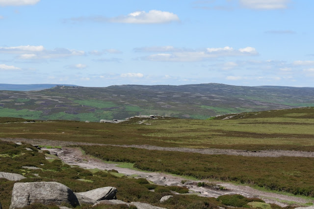 Moorland stretching out into the distance, with a glimpse of another escarpment on its edge.