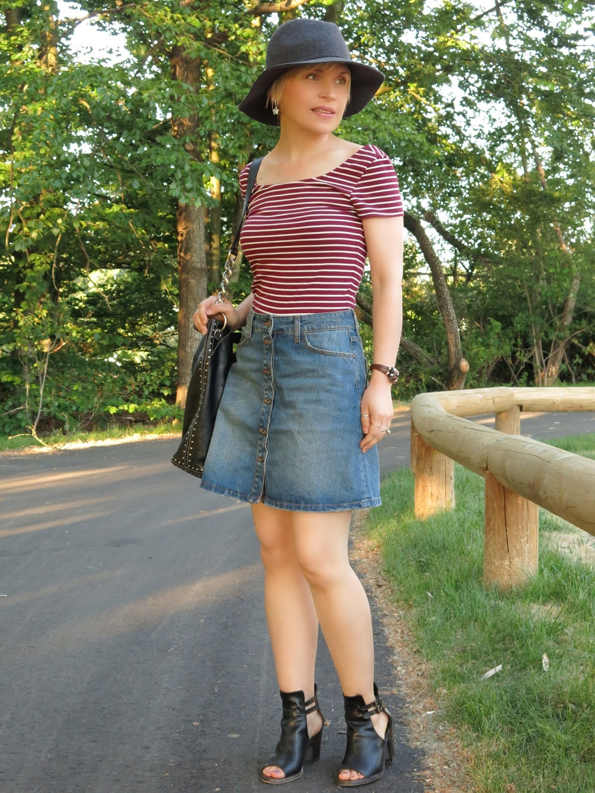 styling a button-front A-line mini skirt with a striped t-shirt and floppy hat