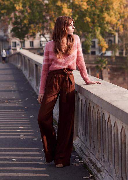 Девушка в коричневых широких брюках фасона paper bag с розовым свитером