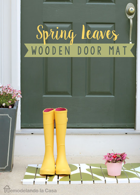 Wooden door mat with leaves design on it. Yellow rainy boots and green door