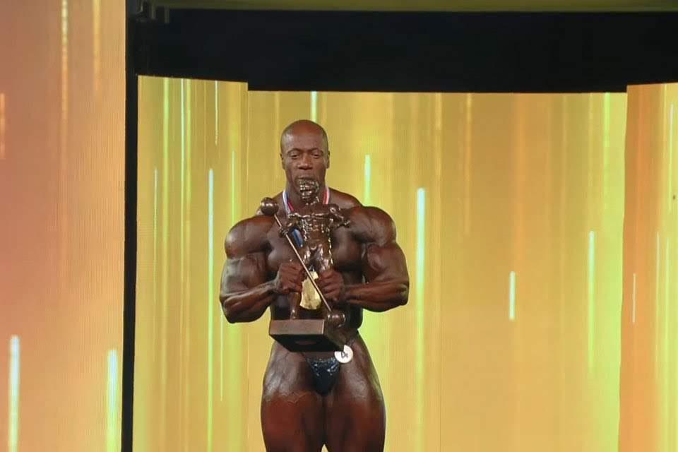 Shawn Rhoden, o Mr. Olympia 2018, ergue o Troféu Sandow. Foto: Reprodução